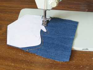 1. Cut out templates for the decorative stitching from heavy paper. Use double sided tape to stick them to the pocket. Stitch along the edge of the guide.